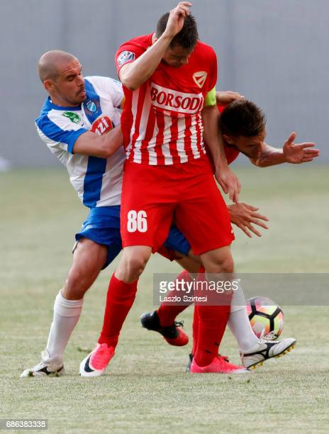 Jozsef Kanta of MTK Budapest tangles with Soma Novothny of DVTK and Mark Tamas of DVTK during the Hungarian OTP Bank Liga match between MTK Budapest...