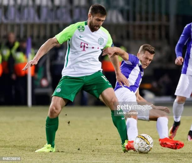 Jozsef Windecker of Ujpest FC slide tackles Daniel Bode of Ferencvarosi TC during the Hungarian OTP Bank Liga match between Ujpest FC and...