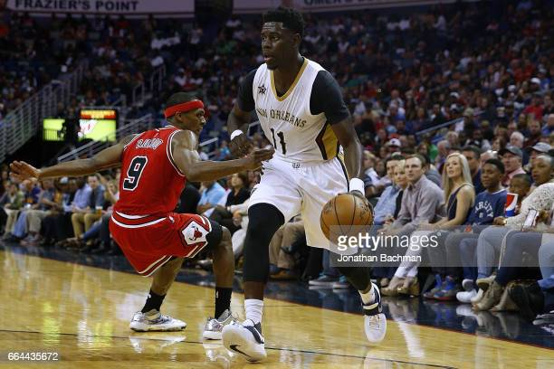 Jrue Holiday of the New Orleans Pelicans drives against Rajon Rondo of the Chicago Bulls during the second half of a game at the Smoothie King Center...