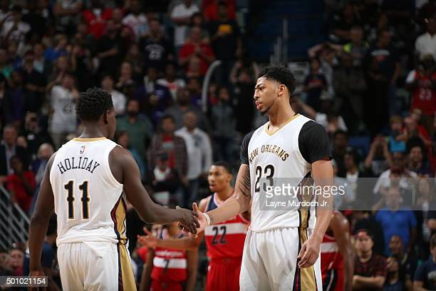 Jrue Holiday of the New Orleans Pelicans high fives Anthony Davis of the New Orleans Pelicans during the game against the Washington Wizards on...
