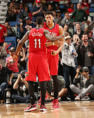 Jrue Holiday of the New Orleans Pelicans high fives teammate Anthony Davis during the game against the Utah Jazz on December 16 2014 at Smoothie King...