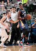 Jrue Holiday of the New Orleans Pelicans posts up against Jose Juan Barea of the Dallas Mavericks on December 10 2014 at the American Airlines Center...