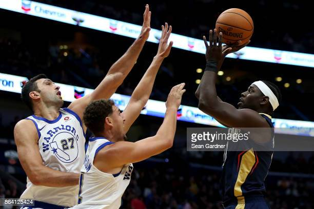 Jrue Holiday of the New Orleans Pelicans shoots over Zaza Pachulia of the Golden State Warriors and Klay Thompson of the Golden State Warriors during...