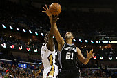 Jrue Holiday of the New Orleans Pelicans shoots the ball over Tim Duncan of the San Antonio Spurs at Smoothie King Center on December 26 2014 in New...
