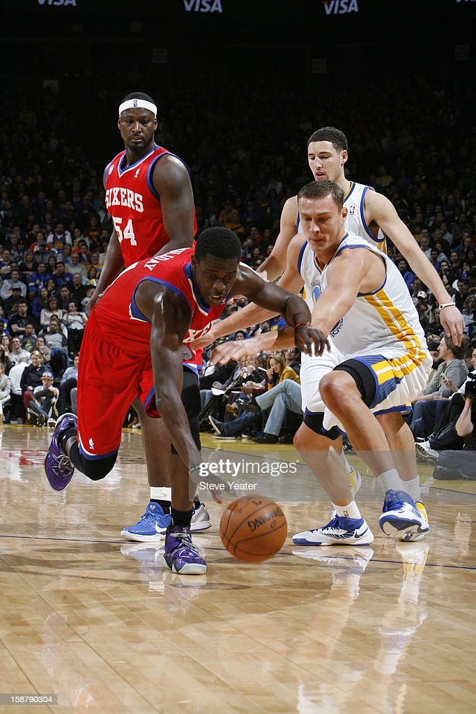 Jrue Holiday #11 of the Philadelphia 76ers chases after a loose ball against Andris Biedrins #15 of the Golden State Warriors on December 28, 2012 at Oracle Arena in Oakland, California.