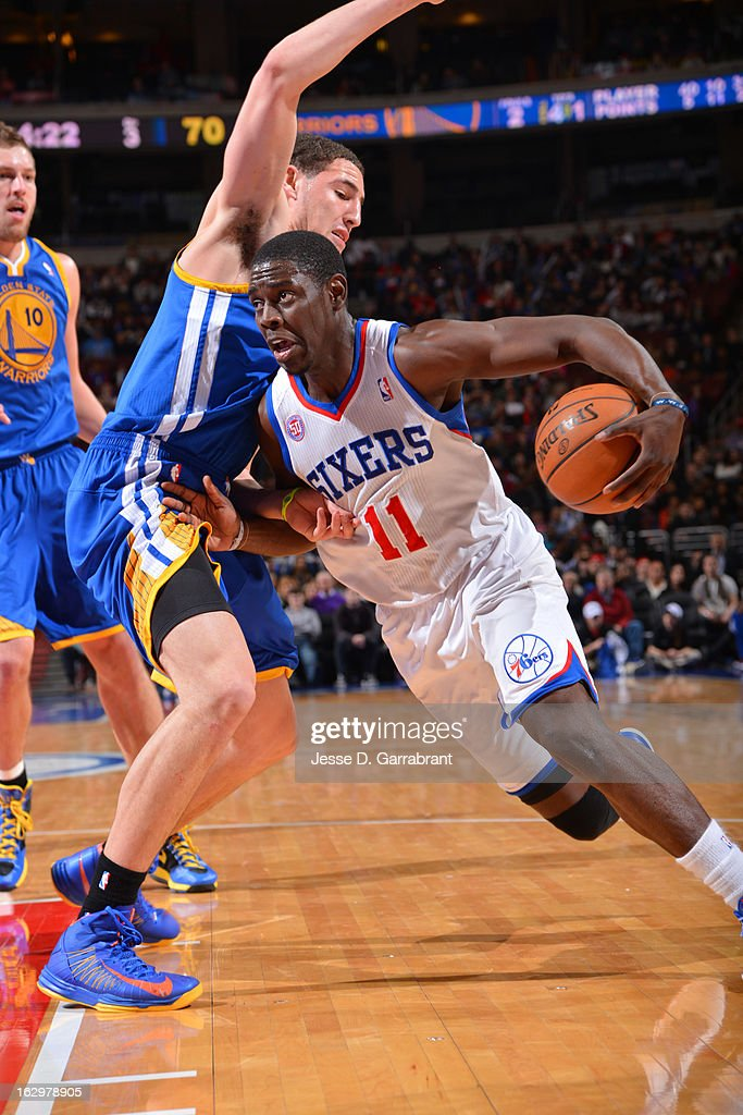 Jrue Holiday #11 of the Philadelphia 76ers drives to the basket against Klay Thompson #11 of the Golden State Warriors on March 2, 2013 at the Wells Fargo Center in Philadelphia, Pennsylvania.