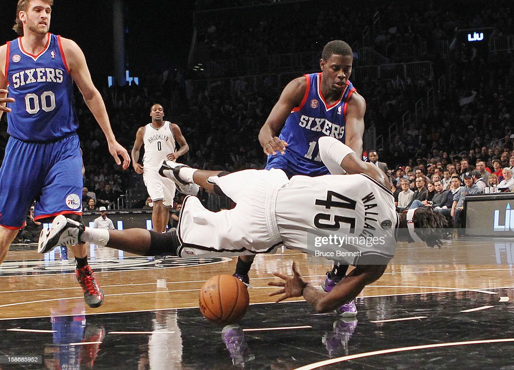 Jrue Holiday of the Philadelphia 76ers fouls Gerald Wallace of the Brooklyn Nets at Barclays Center on December 23 2012 in the Brooklyn borough of...