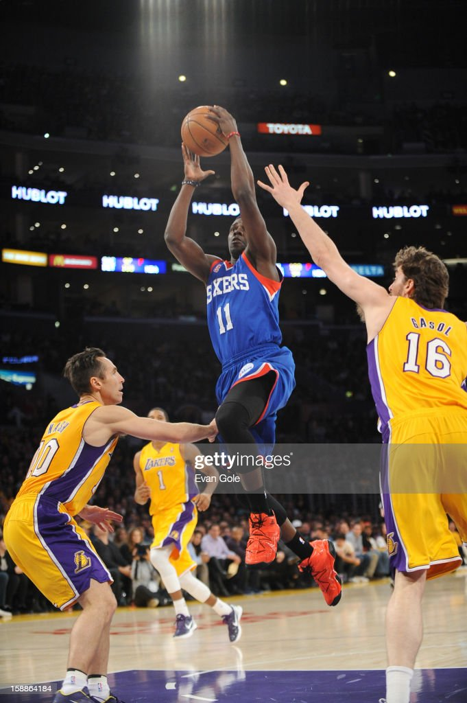 Jrue Holiday #11 of the Philadelphia 76ers goes to the basket against Steve Nash #10 and Pau Gasol #16 of the Los Angeles Lakers during the game between the Philadelphia 76ers and the Los Angeles Lakers at Staples Center on January 1, 2013 in Los Angeles, California.