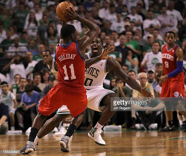 Jrue Holiday of the Philadelphia 76ers looks to pass by Brandon Bass of the Boston Celtics during Game Seven of the Eastern Conference Semifinals...
