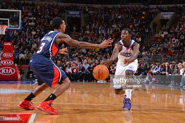 Jrue Holiday of the Philadelphia 76ers passes the ball against Louis Williams of the Atlanta Hawks during the game at the Wells Fargo Center on...