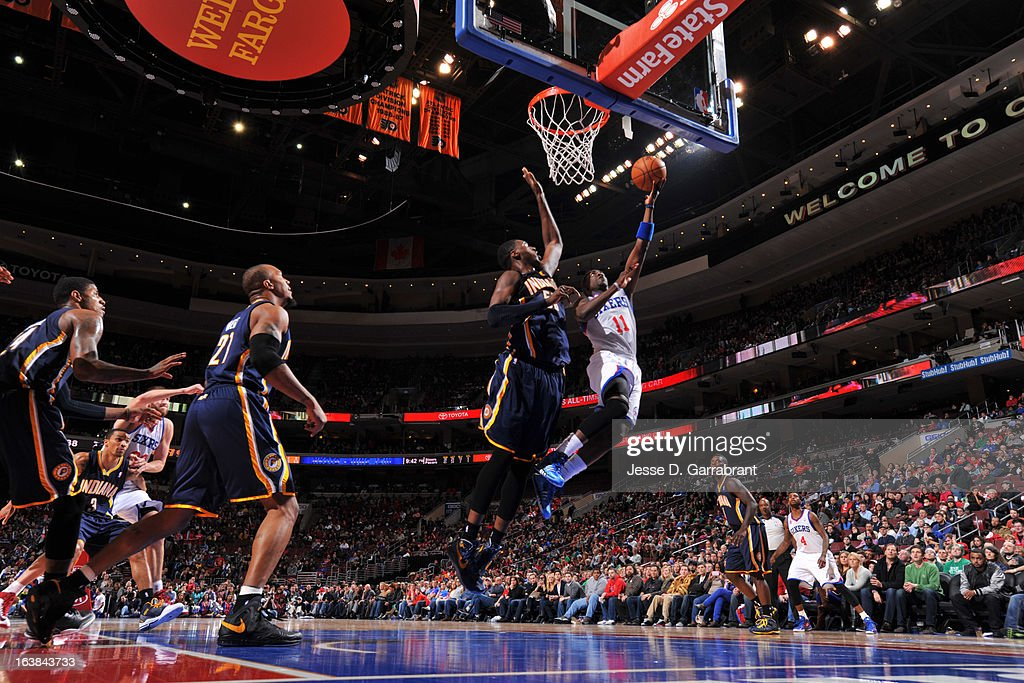 Jrue Holiday #11 of the Philadelphia 76ers shoots a layup against Roy Hibbert #55 of the Indiana Pacers at the Wells Fargo Center on March 16, 2013 in Philadelphia, Pennsylvania.