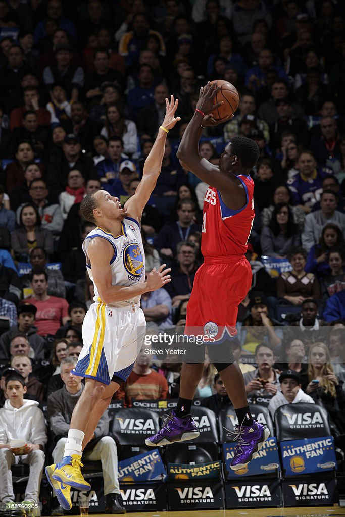 Jrue Holiday #11 of the Philadelphia 76ers shoots against Stephen Curry #30 of the Golden State Warriors on December 28, 2012 at Oracle Arena in Oakland, California.