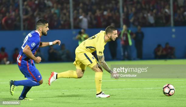 Juan Aguilar of Paraguays Cerro Porteno vies for the ball with Dario Benedetto of Argentina's Boca Juniors during a friendly match at the...