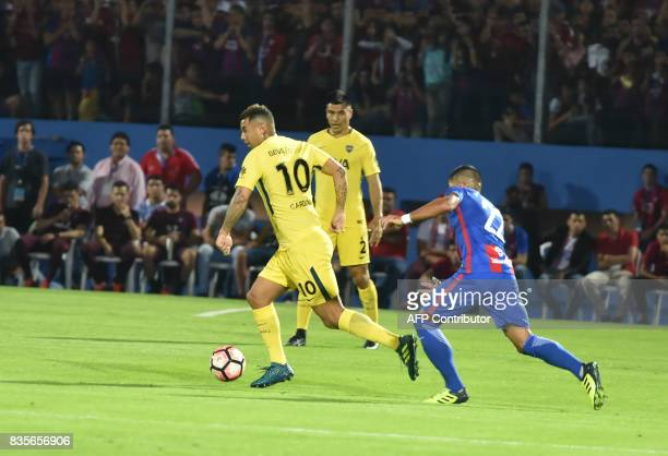 Juan Aguilar of Paraguays Cerro Porteno vies for the ball with Edwin Cardona of Argentina's Boca Juniors during a friendly match for the inauguration...