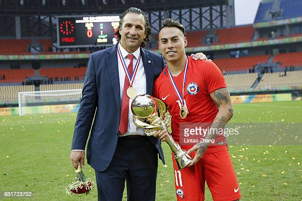 Juan Antonio Pizzi head coach of Chile national football team and player Eduardo Vargas with winner trophy poses for a photo after winning the final...