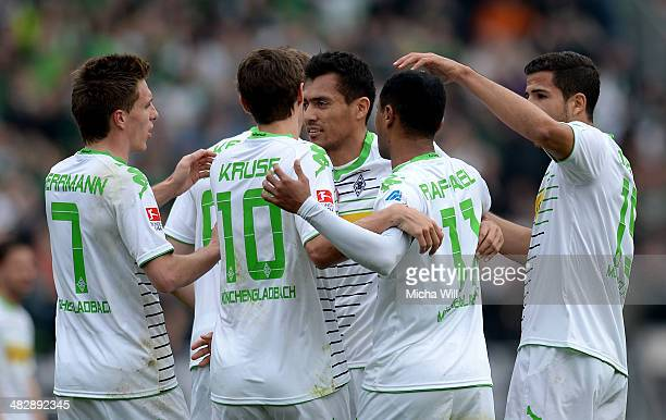 Juan Arango of Moenchengladbach celebrates with teammates after scoring the opening goal from a free kick during the Bundesliga match between 1 FC...