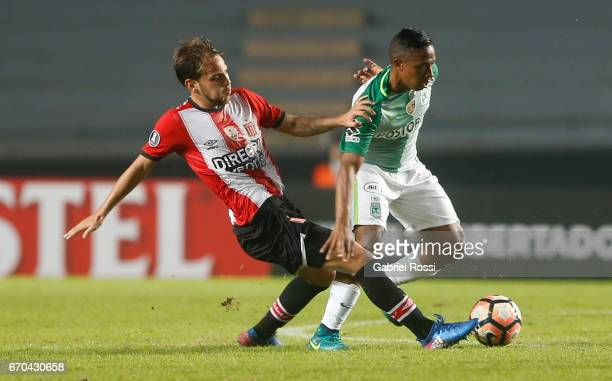 Juan Bautista Cascini of Estudiantes fights for the ball with Andres Ibarguen of Atletico Nacional during a group stage match between Estudiantes and...