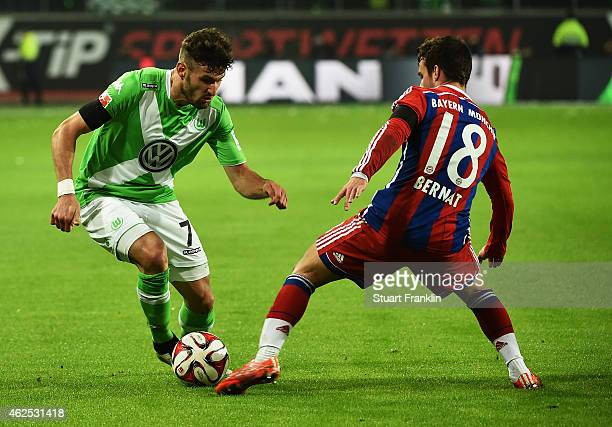 Juan Bernat of Muenchen is challenged by Daniel Caligiuri of Wolfsburg during the Bundesliga match between VfL Wolfsburg and FC Bayern Muenchen at...