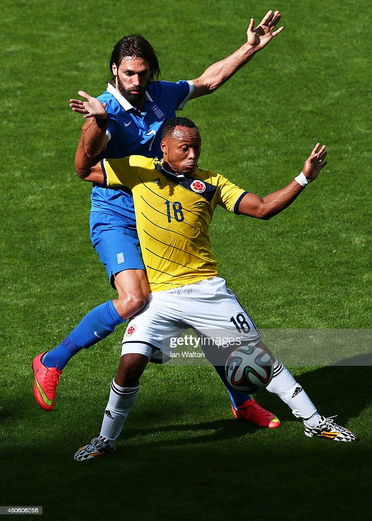 Juan Camilo Zuniga of Colombia holds off a challenge by Giorgos Samaras of Greece during the 2014 FIFA World Cup Brazil Group C match between Colombia and Greece at Estadio Mineirao on June 14, 2014 in Belo Horizonte, Brazil.
