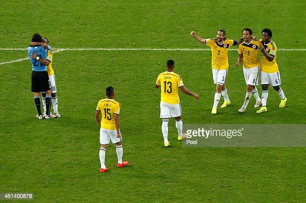 Juan Camilo Zuniga of Colombia hugs Edinson Cavani of Uruguay as teammates Alexander Mejia Fredy Guarin Mario Yepes Abel Aguilar and Carlos Sanchez...