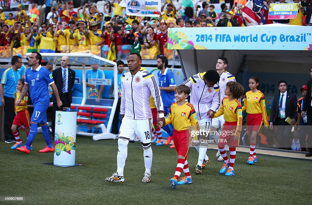 Juan Camilo Zuniga of Colombia walks out to the pitch with a young player escort prior to the 2014 FIFA World Cup Brazil Group C match between...