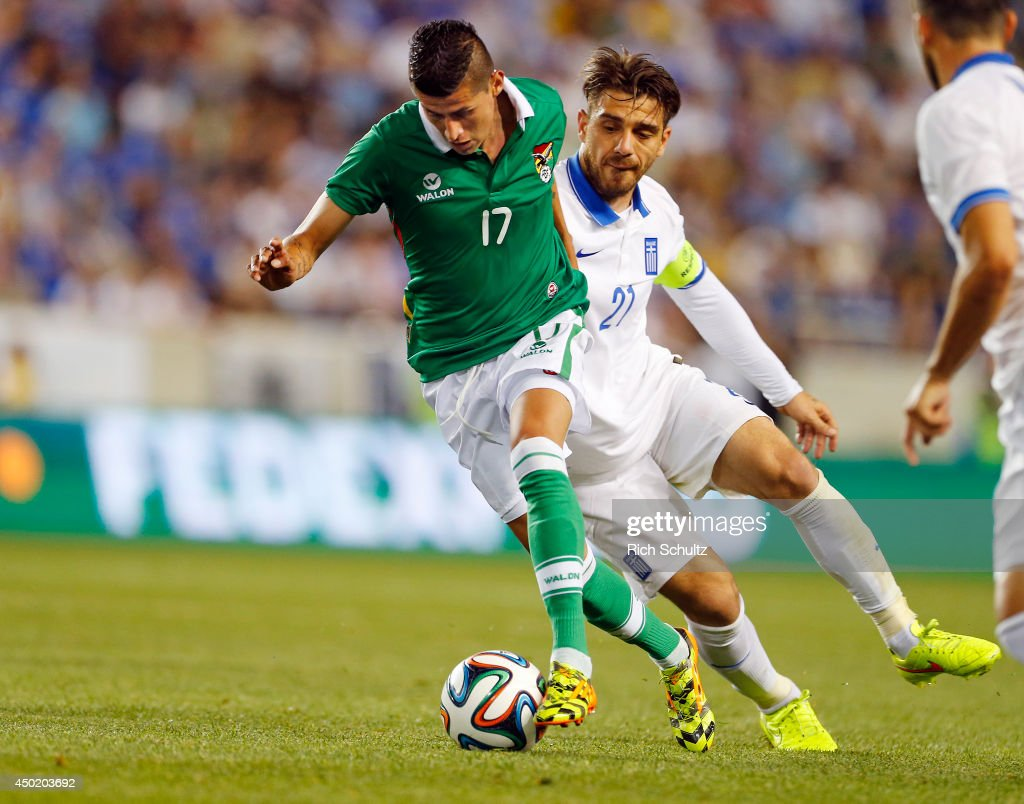 Juan Carlos Arce of Bolivia is defended by Kostas Katsouranis of Greece during the second half of an international friendly match at Red Bull Arena...