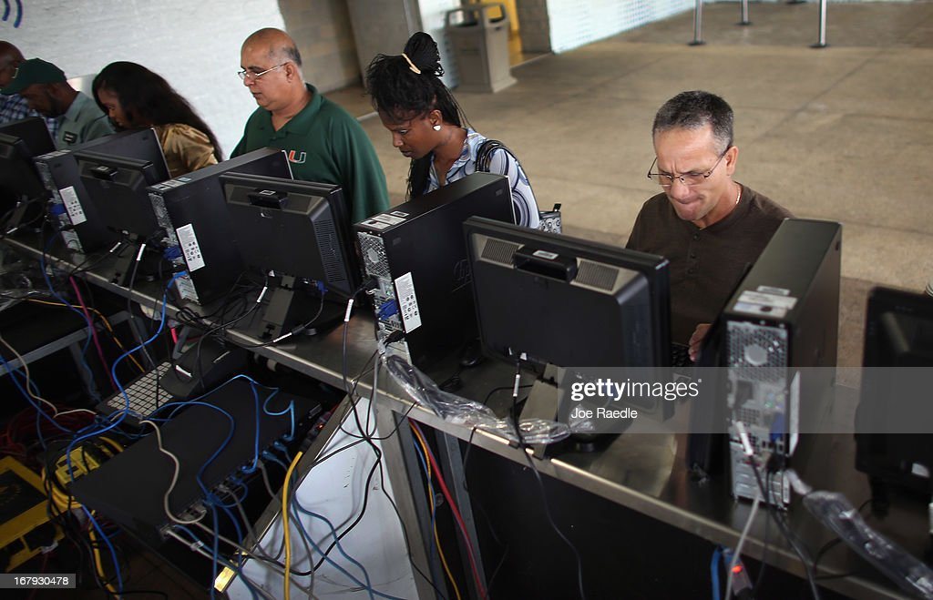 Juan Carlos Cisternas (R) and other people looking for work apply for jobs using computers set up during a job fair at the Miami Dolphins Sun Life stadium on May 2, 2013 in Miami, Florida. If voters approve a hotel tax hike to fund stadium renovations the jobs would be available. If not, the Dolphins management is indicating they would not be able to renovate the stadium nor create the jobs.