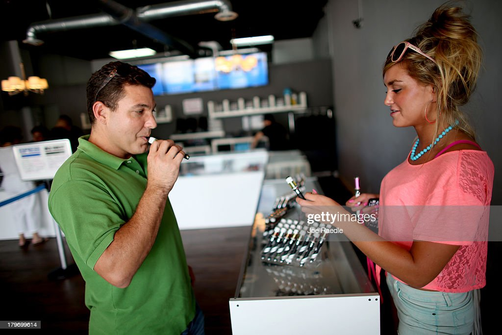 Juan Carlos Fernandez(L) and Chloe Lamb shop for an E liquid flavor for their electronic cigarettes at the Vapor Shark store on September 6, 2013 in Miami, Florida. E-cigarette manufacturers have seen a surge in popularity for the battery-powered devices that give users a vapor filled experience with nicotine and other additives, like flavoring.