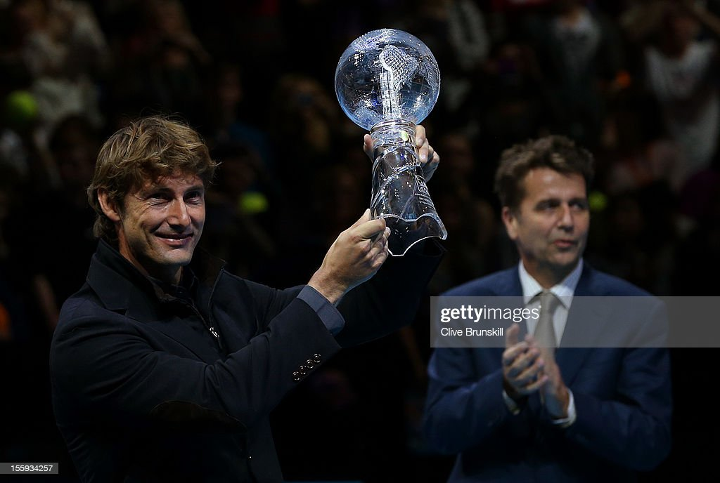 Juan Carlos Ferrero of Spain poses with a trophy presented to him by ATP Executive Chairman and President Brad Drewett to mark his retirement from...