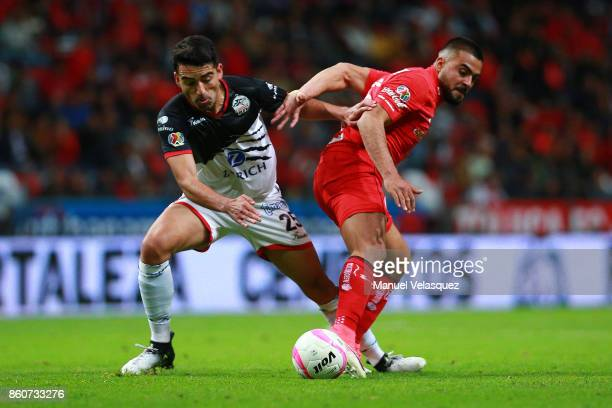 Juan Carlos Garcia of Lobos BUAP struggles for the ball with Alexis Canelo of Toluca during the 13th round match between Toluca and Lobos BUAP as...