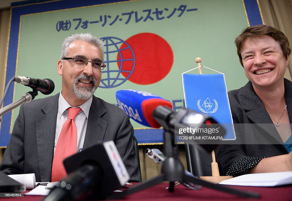 Juan Carlos Lentijo, a team leader of International Atomic Energy Agency (IAEA) mission on remediation of large contaminated areas in and around the Fukushima Daiichi nuclear power plant, shares a smile with the team's public information officer Gill Tudor (R), during a press conference following the announcement of a preliminary summary report in Tokyo on October 21, 2013. Heavy rain at the Fukushima nuclear plant caused a leak of radioactive water containing a cancer-causing isotope, possibly into the sea, its operator said on October 21, as a typhoon approaching Japan threatened further downpours. AFP PHOTO / TOSHIFUMI KITAMURA