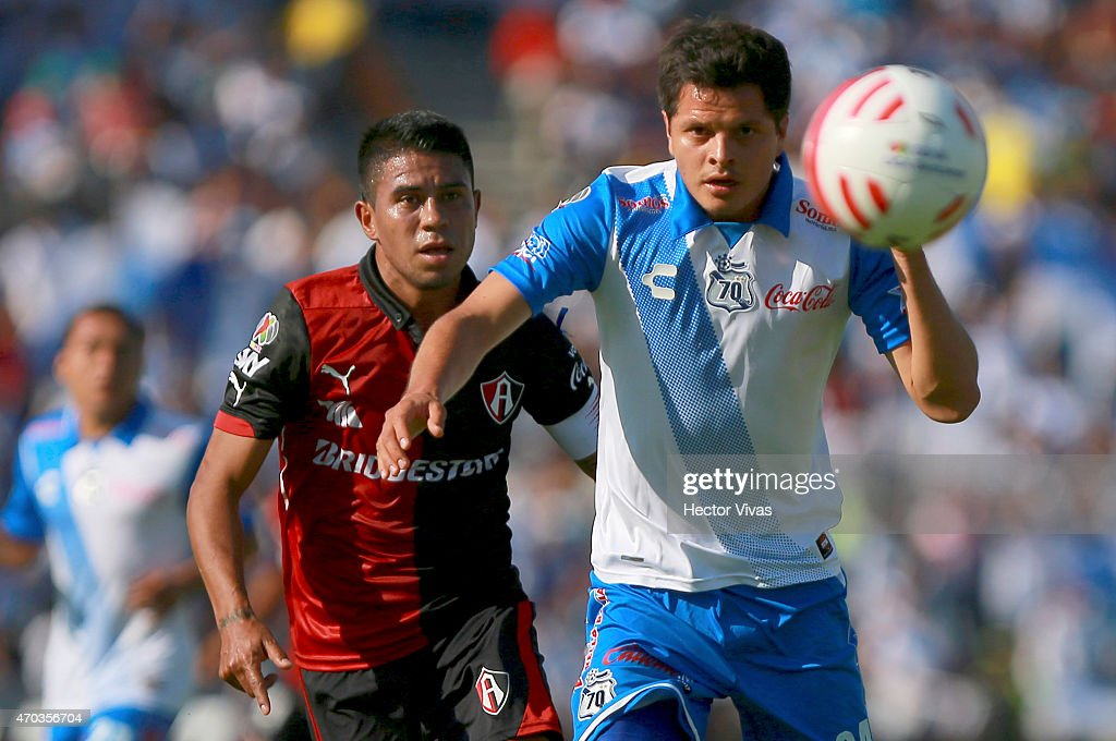 Juan Carlos Medina of Atlas struggles for the ball with Sergio Perez of Puebla during a match between Puebla and Atlas as part of 14th round Clausura...