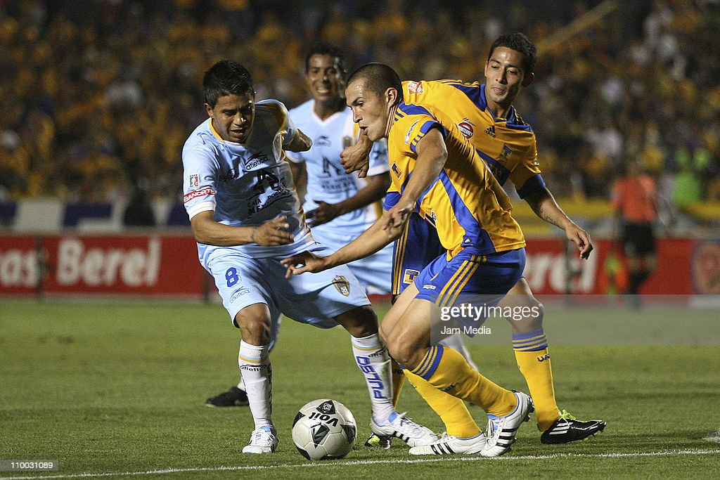 Juan Carlos Medina (I) of San Luis struggles for the ball with David Toledo (I) and Jorge Torres (C) of Tigres during the Clausura 2011 Tournament in the Mexican Football League at Universitary Stadium on March 12, 2011 in Monterrey, Mexico.