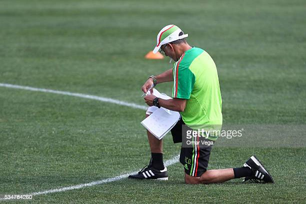 Juan Carlos Osorio coach of Mexico writes down notes during a Mexico National Team training session at Emory University on May 27 2016 in Atlanta...