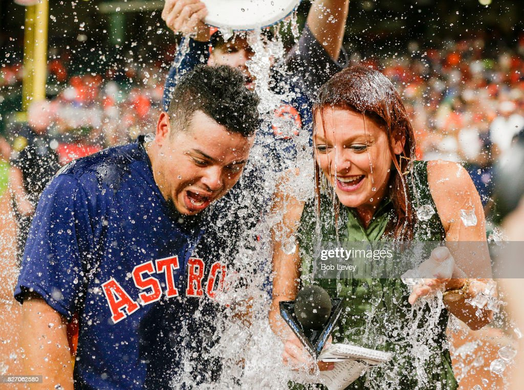 Juan Centeno #30 of the Houston Astros and AT&T SportsNet sideline reporter Julia Morales are doused with water from Collin McHugh during a post game interview at Minute Maid Park on August 6, 2017 in Houston, Texas. Centeno hit a walkoff single in the ninth inning against the Toronto Blue Jays.