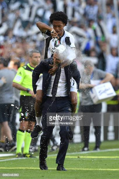 Juan Cuadrado and head coach Massimiliano Allegri of Juventus FC celebrate after beating FC Crotone 30 to win the Serie A Championships at the end of...