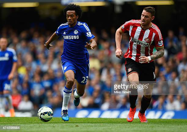 Juan Cuadrado of Chelsea and Connor Wickham of Sunderland compete for the ball during the Barclays Premier League match between Chelsea and...