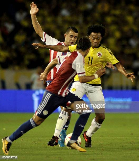 Juan Cuadrado of Colombia fights for the ball with Gustavo Gomez of Paraguay during a match between Colombia and Paraguay as part of FIFA 2018 World...