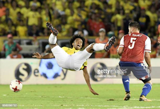 Juan Cuadrado of Colombia struggles for the ball with Bruno Valdez of Paraguay during a match between Colombia and Paraguay as part of FIFA 2018...