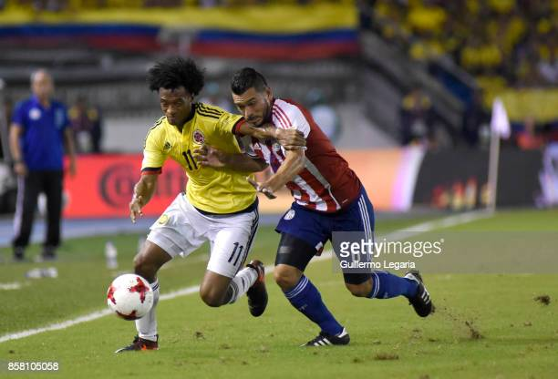 Juan Cuadrado of Colombia struggles for the ball with Miguel Samudiio of Paraguay during a match between Colombia and Paraguay as part of FIFA 2018...