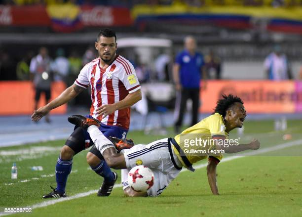Juan Cuadrado of Colombia struggles for the ball with Miguel Samudio of Paraguay during a match between Colombia and Paraguay as part of FIFA 2018...