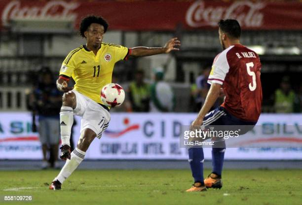 Juan Cuadrado of Colombia vies for the ball with Bruno Valdez of Paraguay during a match between Colombia and Paraguay as part of FIFA 2018 World Cup...