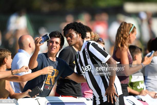 Juan Cuadrado of Juventus A poses for a selfie with a fan during the preseason friendly match between Juventus A and Juventus B on August 17 2017 in...