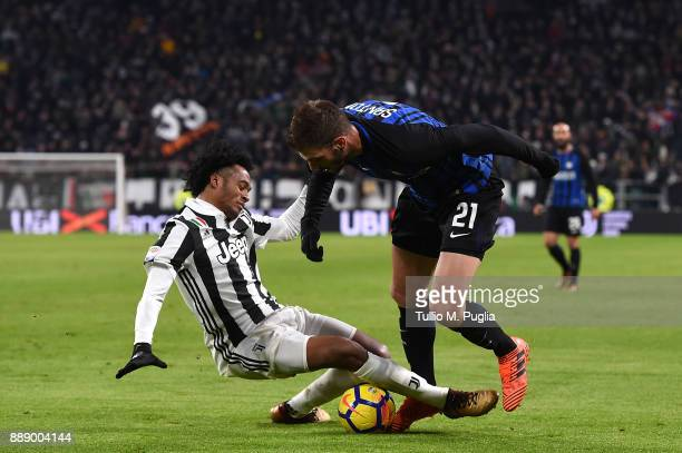 Juan Cuadrado of Juventus and Davide Santon of Internazionale compete for the ball during the Serie A match between Juventus and FC Internazionale at...