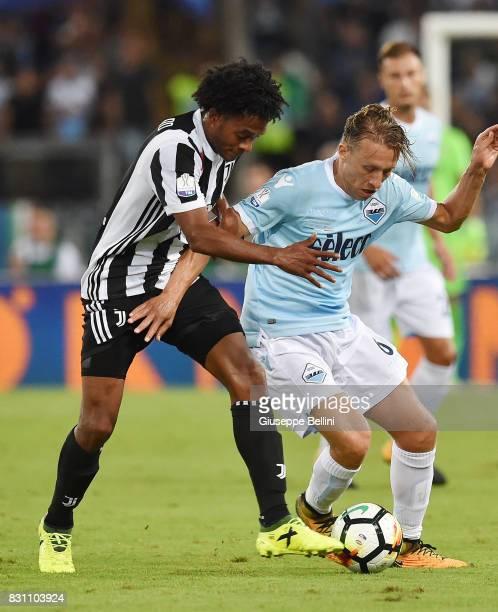 Juan Cuadrado of Juventus and Lucas Pezzini Leiva of SS Lazio in action during the Italian Supercup match between Juventus and SS Lazio at Stadio...