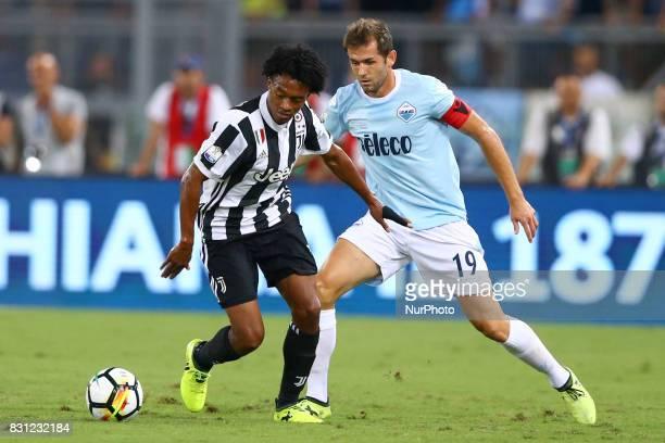 Juan Cuadrado of Juventus and Senad Lulic of Lazio during the Italian Supercup match between Juventus and SS Lazio at Stadio Olimpico on August 13...