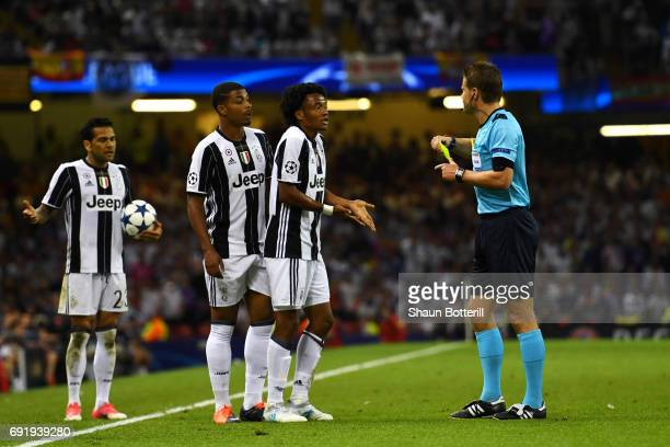 Juan Cuadrado of Juventus argues with referee Felix Brych during the UEFA Champions League Final between Juventus and Real Madrid at National Stadium...