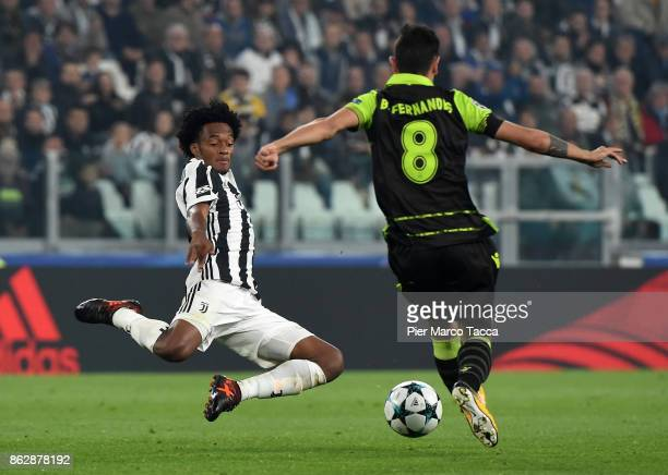 Juan Cuadrado of Juventus competes for the ball with Bruno Fernandes of Sporting CP during the UEFA Champions League group D match between Juventus...