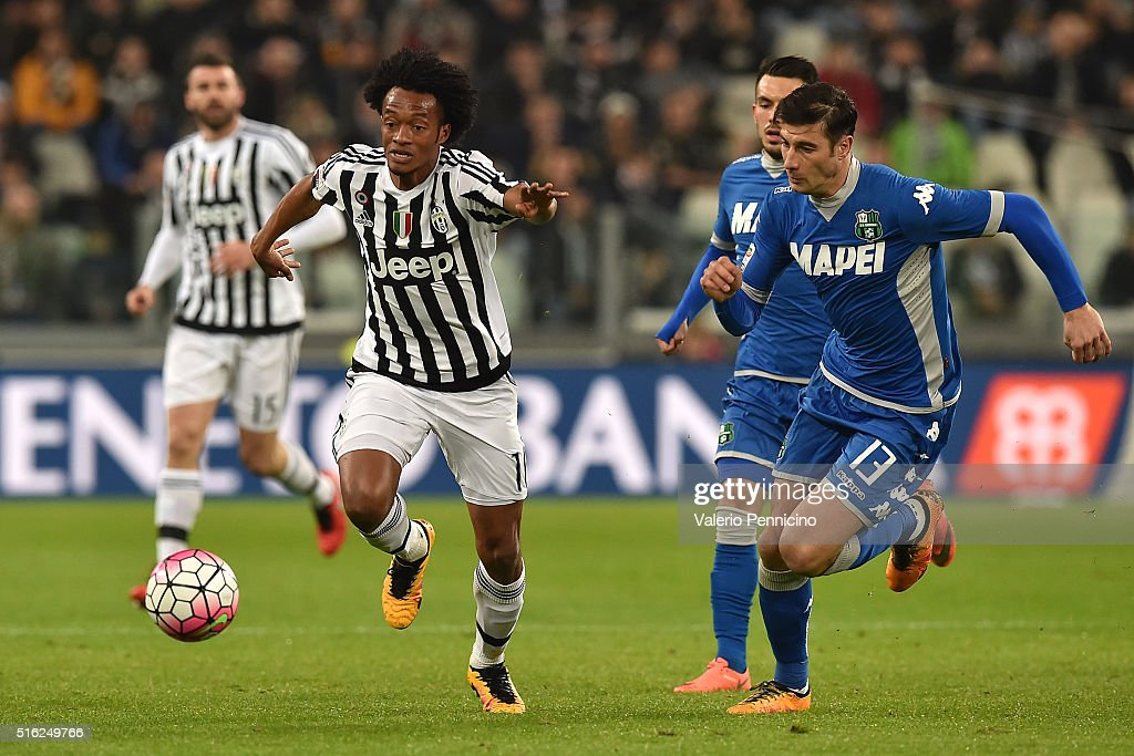 Juan Cuadrado (L) of Juventus FC in action against <a gi-track='captionPersonalityLinkClicked' href=/galleries/search?phrase=Federico+Peluso&family=editorial&specificpeople=6336600 ng-click='$event.stopPropagation()'>Federico Peluso</a> of US Sassuolo Calcio during the Serie A match between Juventus FC and US Sassuolo Calcio at Juventus Arena on March 11, 2016 in Turin, Italy.