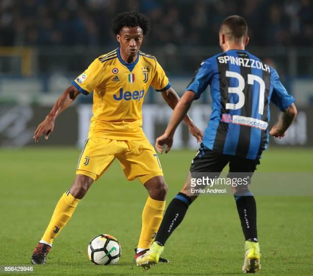 Juan Cuadrado of Juventus FC is challenged by Leonardo Spinazzola of Atalanta BC during the Serie A match between Atalanta BC and Juventus at Stadio...